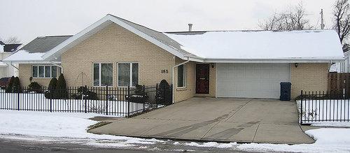 Une maison de banlieue américaine en hiver, avec une large allée de garage dépourvue de neige